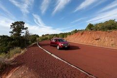 红色路柏油碎石地面的汽车高山 免版税库存照片