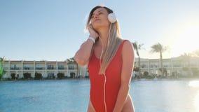 红色跳舞在清楚的蓝色游泳场附近的泳装和耳机的美女,有乐趣和听的音乐  影视素材