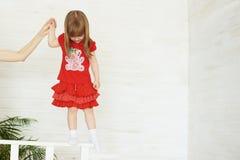 红色身分的年轻逗人喜爱的女孩在栏杆 库存照片