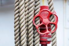 红色轮子、停止阀和绳索在一艘高船 免版税库存图片