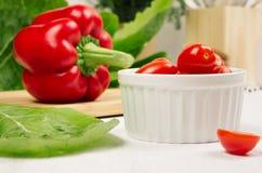 红色辣椒粉胡椒、西红柿和新鲜的叶子沙拉在白色木板,特写镜头 库存照片