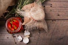 红色辣辣椒鹌鹑蛋特写镜头在一个玻璃瓶子的,迷迭香的壳和枝杈在木背景的 免版税库存照片