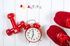红色运动鞋、时钟和哑铃在木backgroyund 是活跃的 免版税库存图片