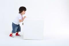 红色运动鞋的小男孩推挤大白色立方体 免版税库存照片