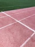 红色连续轨道在体育场内 您的设计的纹理 库存图片