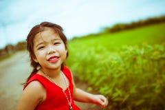红色选矿的微笑的孩子女孩有赞成绿草背景 图库摄影