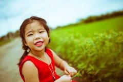 红色选矿的微笑的孩子女孩有赞成绿草背景 免版税库存图片