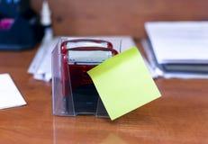 红色邮票在桌上的本文与一个绿色贴纸 办公室和学校概念 库存图片