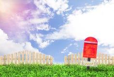红色邮箱和木在有尖桩篱栅和迷离天空的庭院在天 库存照片