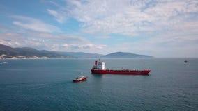 红色邮轮船鸟瞰图在水,近拖引船的,对口岸的入口 股票录像