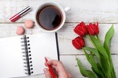 红色郁金香、咖啡杯和笔记本在白色木桌 平的位置 免版税库存图片