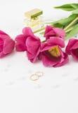 红色郁金香、婚戒、香水和小珠 免版税库存照片