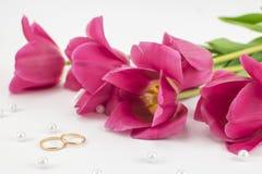 红色郁金香、婚戒、香水和小珠 免版税库存图片