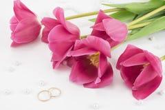 红色郁金香、婚戒、香水和小珠 库存照片
