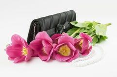 红色郁金香、提包和小珠在白色背景 免版税库存图片