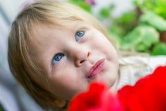 红色郁金香的美丽的婴孩 免版税库存照片
