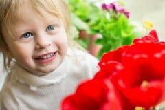 红色郁金香的美丽的婴孩 库存图片