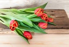 红色郁金香花束在土气木板的 免版税图库摄影