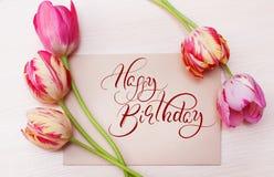 红色郁金香花束在白色背景的与文本生日快乐 书法字法 库存照片