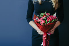 红色郁金香花束在girs手上 无法认出 免版税图库摄影