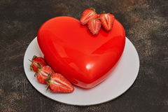 红色釉奶油甜点蛋糕,心脏在黑暗的背景的形状形式 免版税图库摄影