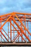 红色金属桥梁 背景蓝色覆盖天空 图库摄影