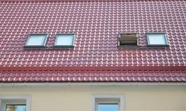 红色金属铺磁砖了有新的屋顶窗的屋顶,屋顶Windows,天窗、雨天沟系统和屋顶保护免受雪板 免版税图库摄影
