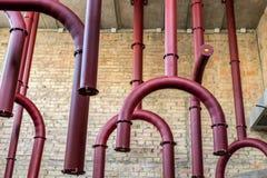 红色金属从天花板用管道输送垂悬反对砖墙背景 免版税图库摄影
