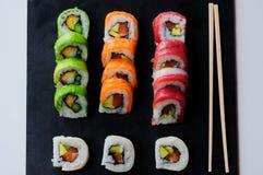 红色金枪鱼、三文鱼、鲕梨和黄油寿司卷在板岩盘钓鱼 日本食物 图库摄影