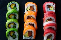 红色金枪鱼、三文鱼、鲕梨和黄油寿司卷在板岩盘钓鱼 日本食物 免版税库存照片