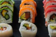 红色金枪鱼、三文鱼、鲕梨和黄油寿司卷在板岩盘钓鱼 日本食物 库存图片