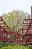 红色钢&big绿色树 库存照片