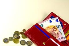 红色钱包妇女 钞票十和五欧元 一些枚硬币 米黄背景 库存照片