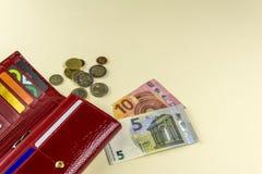 红色钱包妇女 钞票十和五欧元 一些枚硬币 米黄背景 图库摄影