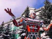 红色铁金属从一辆汽车的大强的危险意想不到,未来派有人的特点的机器人用手和头在冬天 免版税库存照片
