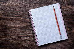 红色铅笔和被摆正的笔记薄在木的杉木 库存图片