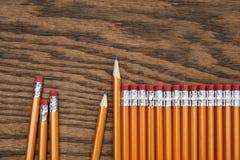 红色铅笔行木表面上的 免版税图库摄影
