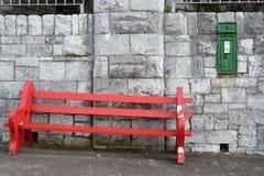 红色长凳对墙壁 免版税图库摄影