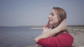 红色长的礼服跳舞的特写镜头画象逗人喜爱的graseful妇女在壮观的看法附近举在大石头的手  股票视频
