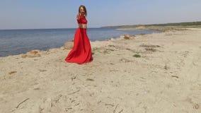 红色长的礼服跳舞的画象graseful年轻女人在蓝色海附近壮观的看法举在大石头的手 股票视频