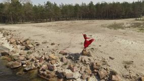 红色长的礼服跳舞的精美graseful妇女在蓝色海水附近壮观的看法举在大石头的手 股票视频