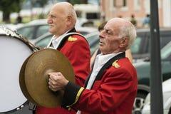 红色长袍的老音乐家 库存图片
