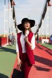 红色长裤套装和黑帽会议的时兴的加工好的深色的女孩 免版税库存图片