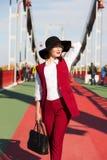 红色长裤套装和黑帽会议pos的时髦的加工好的深色的妇女 免版税库存图片