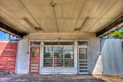 红色门,在被放弃的加油站的白色门 图库摄影