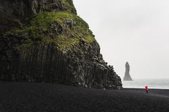 红色雨衣的妇女为黑玄武岩专栏照相的在黑沙滩在维克,冰岛 图库摄影