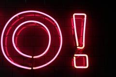 红色霓虹灯信件和感叹号在黑墙壁上 免版税库存照片