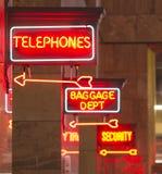 红色霓虹灯广告室内集中处标志箭头指向行李电话 免版税库存图片