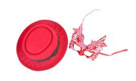红色面具和在白色背景隔绝的五颜六色的红色帽子顶视图 免版税库存图片