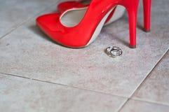 红色鞋子和婚戒 免版税库存图片
